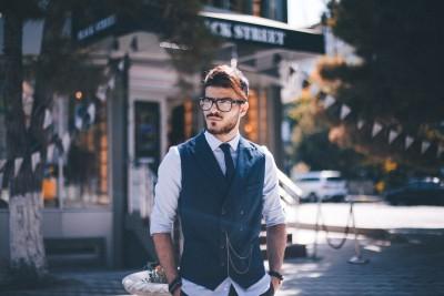 ein konventionell attraktiver Mann in Anzug und Weste steht an einer Straßenecke