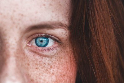 Eine Nahaufnahme des Auges einer jungen Frau mit rotem Haar und Sommersprossen
