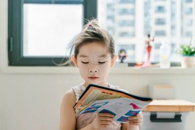 Ein Kind liest ein Buch in einem sonnendurchfluteten Raum