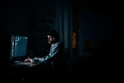 Ein Mann sitzt in einem dunklen Raum im Licht eines Computerbildschirms