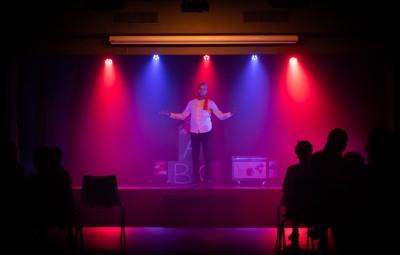 Ein Stand-Up Komiker steht auf einer  Bühne vor einem Publikum