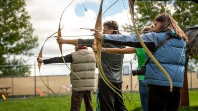 Mehrere Personen schießen Pfeil und Bogen auf eine Zielscheibe